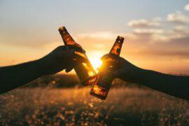 foto av personer som har rukket ølsalget i solnedgangen.