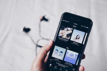 iPhone med musikk app og hodetelefoner
