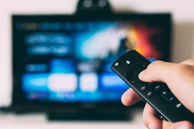 person strømmer serie på tv med fjernkontroll