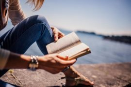 dame som leser bok på svaberget